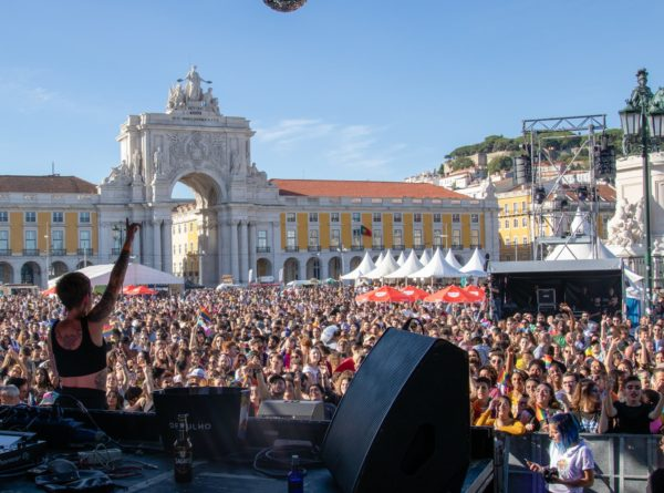 Milhares de pessoas no Arraial Lisboa Pride 2019, fotografia tirada do palco, com o Terreiro do Paço ao fundo