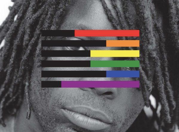 Pessoa Negra por detrás do logótipo do observatório da discriminação, composto pela bandeira LGBTI
